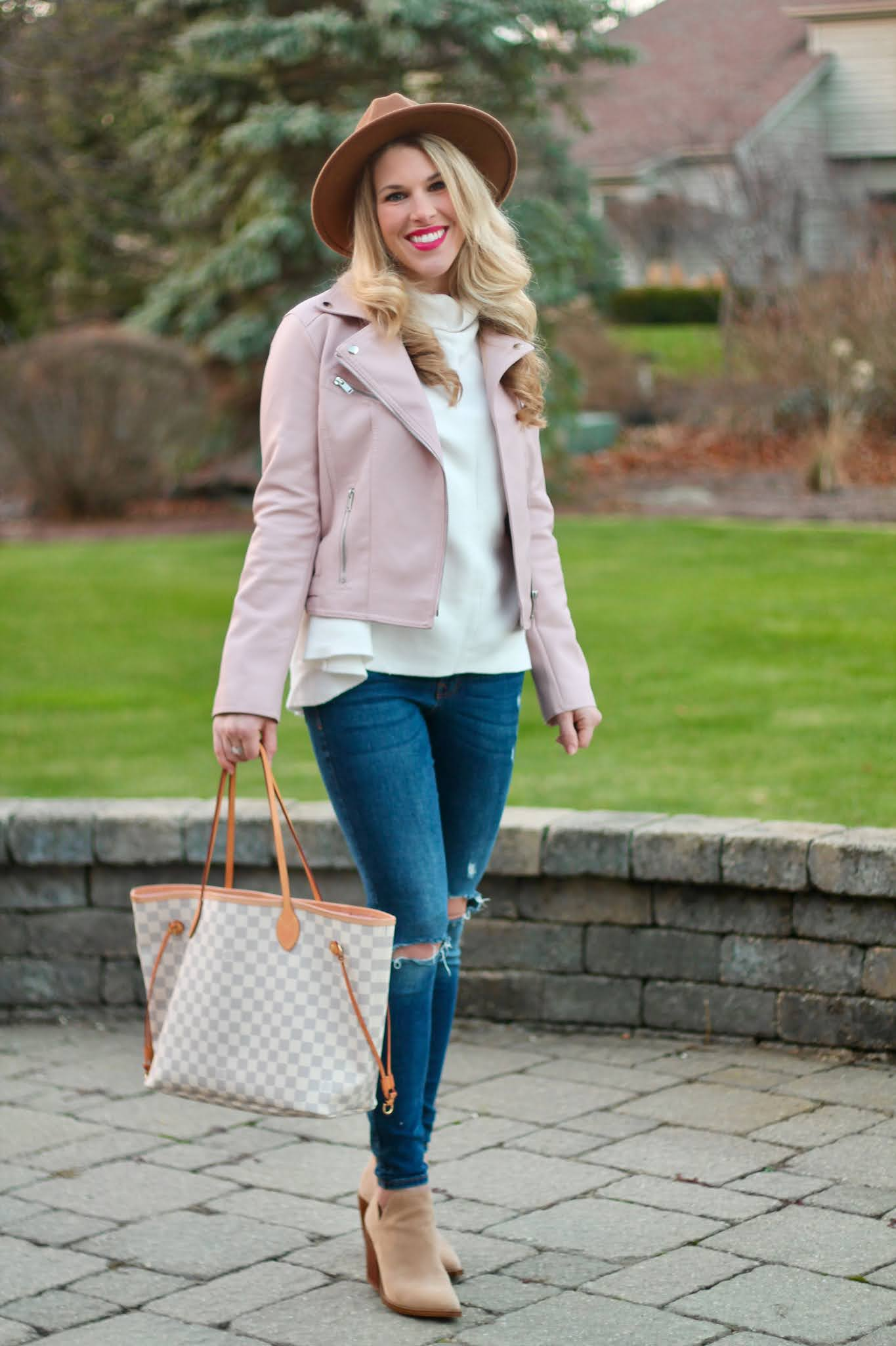 pink moto jacket, white turtleneck tunic, taupe booties, distressed jeans